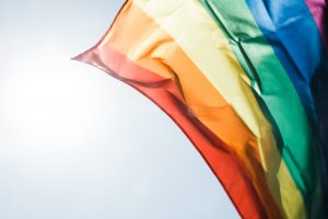 rainbow flag red orange yellow green blue and pink in the wind with blue sky background