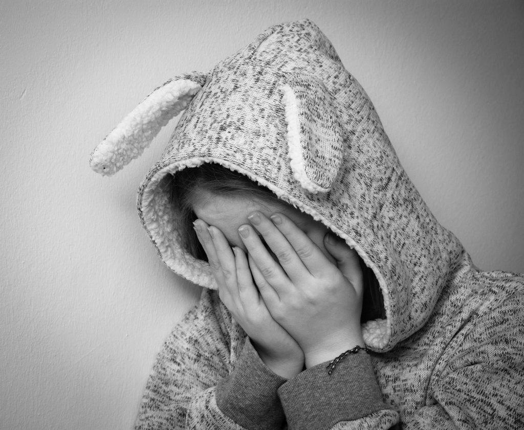 black and white image of child wearing a hooded jumper with bunny ears attached with their hands covering their face
